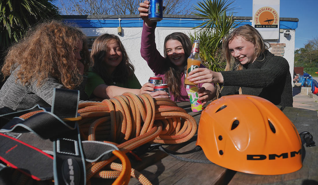 4 girls enjoying a drink after a rock climbing excursion outside The Paddlers Return